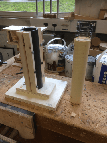 A plastic mould for a thin, circular pillar, with a cast plaster-of-paris pillar next to it